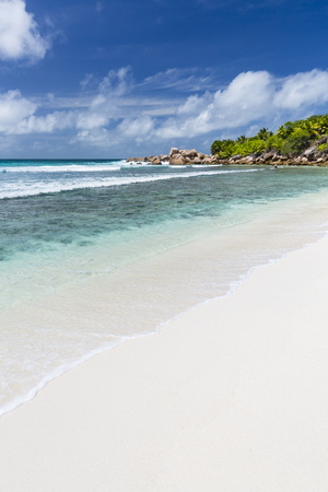 la digue: Perfect white beach Anse Cocos in La Digue, Seychelles with granite boulders and palm trees Stock Photo