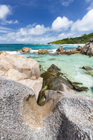 la digue: Tube like granite rock in the foreground with turquoise water at Anse Cocos in La Digue, Seychelles Stock Photo