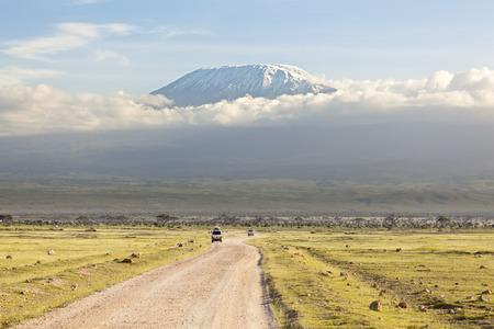 フォア グラウンドで道路とケニアのアンボセリ国立公園から見た雪のキャップとキリマンジャロ。