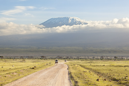 Kilimanjaro with snow cap seen from Amboseli National Park in Kenya with a road in the foreground. Standard-Bild