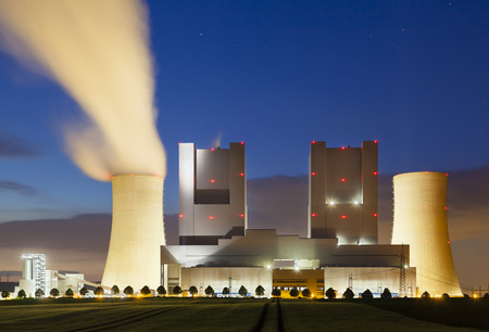 A coal-fired power station behind a field at night