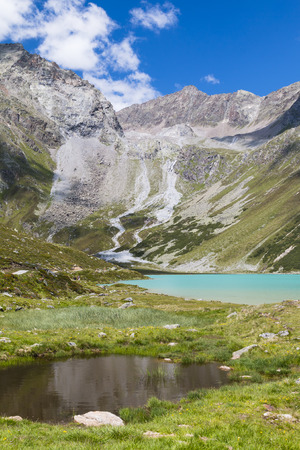 Lake Rifflsee in the Pitztal in Austria with deep blue sky and a little pond in the foreground