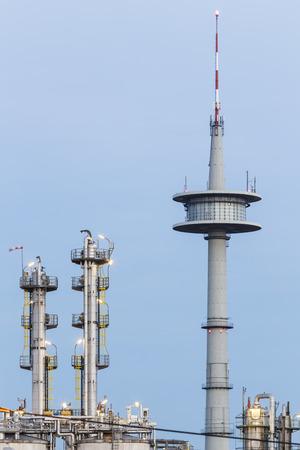 destilacion: torres de destilación en una planta química y una torre de comunicaciones en el fondo con el cielo azul de la noche.