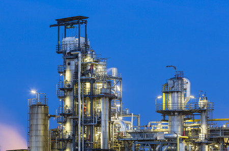 distillation: Ver a las torres de destilaci�n de una planta qu�mica y refiner�a con la noche el cielo azul y la iluminaci�n.