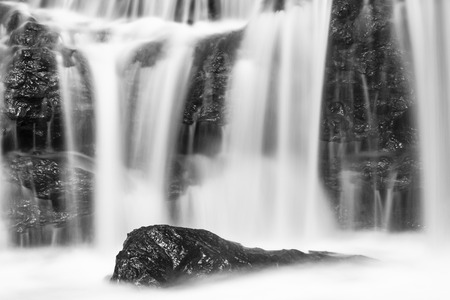 waterfall  dirty: Black and white long exposure detail shot of a small Nairobi River waterfall in Karura Forest, Kenya. Stock Photo