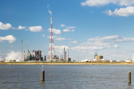 destilacion: Una refinería con la flama de altura de pila en el puerto de Amberes, Bélgica, con un montón de torres de destilación. Foto de archivo