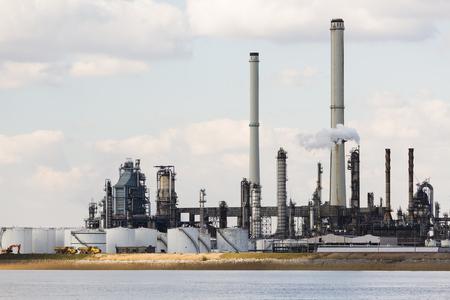 destilacion: Una gran refinería de petróleo con pilas de humo en el puerto de Amberes, Bélgica, con un montón de torres de destilación.