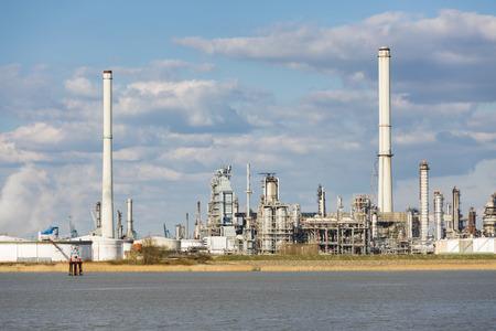 destilacion: Una gran refinería de petróleo con los tanques de almacenamiento de petróleo en el puerto de Amberes, Bélgica, con un montón de torres de destilación.
