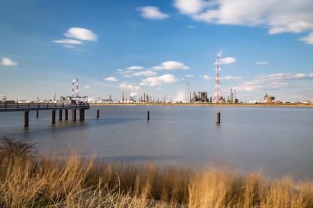 destilacion: La exposición a largo tiro de una gran refinería con tanques de almacenamiento de gas en el puerto de Amberes, Bélgica, con un montón de torres de destilación y un embarcadero en el primer plano.