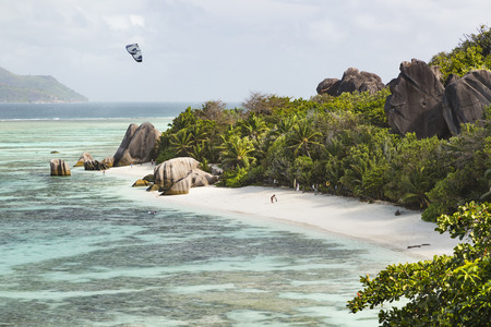 d'argent: High angle view of the famous Anse Source DArgent in La Digue, Seychelles with a kite surfer and some early tourists Stock Photo