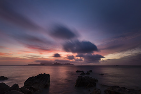 la digue: Colorful sunset long exposure with view to Praslin from La Digue, Seychelles with granite rocks in the foreground