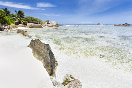 la digue: Tropical white beach Anse Pierrot in La Digue, Seychelles with some granite rocks leading into the image Stock Photo