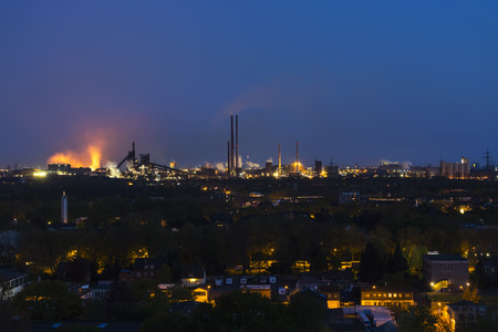 View of a large coking and steel plant in Duisburg, Germany in the night with tapping resulting in the red glow. Editorial