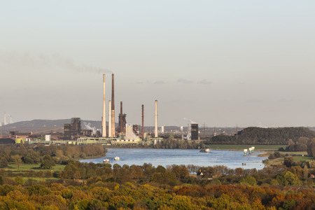 coking: Steaming Coking Plant at the river Rhine near Duisburg, Germany with some ships on the river. Stock Photo
