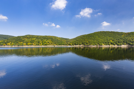 Lake Rursee shore with reflection, perfect blue sky and sunlight in summer seen from a boat. Stock Photo