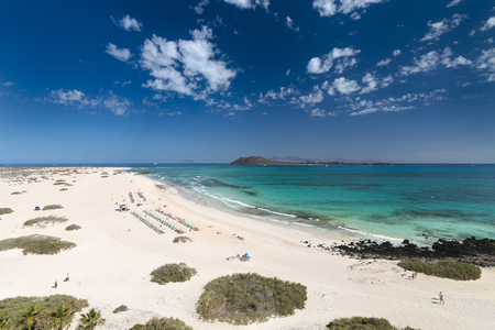 コラレホ ビーチとバック グラウンドでフェルテベントゥラ島、イスラ ・ デ ・ ロボスとランサローテ島とスペインの青緑色の水と砂丘の空撮。 写真素材