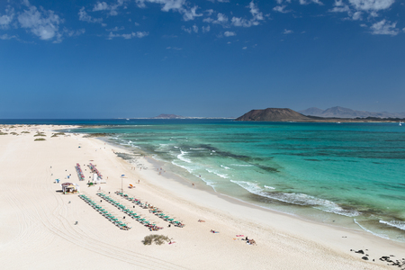 Aerial view of Corralejo Beach and turquoise water in Fuerteventura, Spain with Isla de Lobos and Lanzarote in the background.
