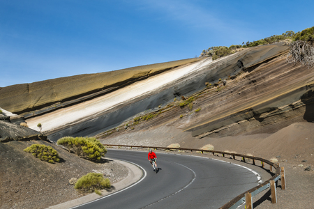 TENERIFE - OCTOBER 14: A mountain biker cycling between colorful volcanic rock layers in a bend of the TF24 road in Tenerife, Spain on October 14, 2014