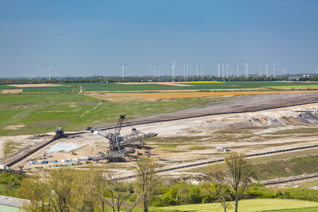 A refilled lignite pit mine in front of a large wind turbine park showing the change from fossil fuels to renewable energies Stock Photo