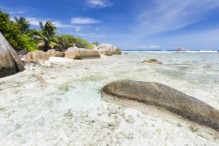 Perfect white beach Anse Pierrot near Source DArgent in La Digue, Seychelles with a granite rock in the foreground