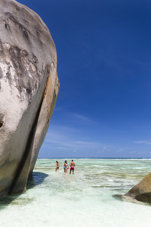 LA DIGUE - AUGUST 12: Tourists walking through the water at the beautiful white beach Anse Source DArgent with scenic granite rocks in La Digue, Seychelles on August 12, 2014