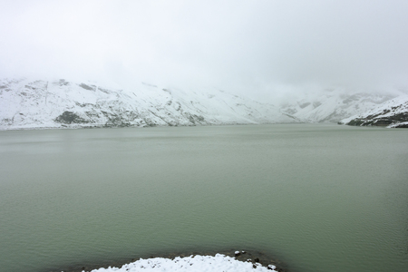 The Silvretta Reservoir Lake near Galtur, Austria with snow in the middle of summer.