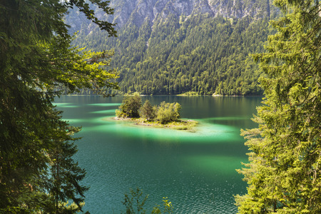 Lake Eibsee with turquoise color and an island near the Wetterstein in Garmisch-Partenkirchen, Germany in summer.
