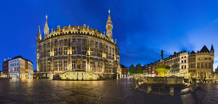 AACHEN - JUNE 05: Panoramic view of the famous old town hall of Aachen, Germany with night blue sky on the market square with the Karlsbrunnen to the right on June 05, 2017.
