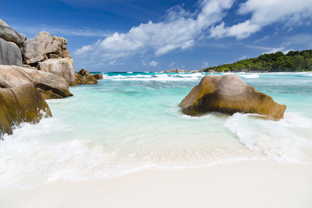 Granite boulders, white beach and emerald water at Anse Cocos in La Digue, Seychelles