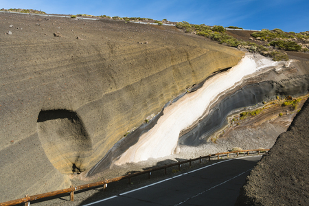 Colorful volcanic rock layers with a white stripe in a bend of the TF24 road in Tenerife, Spain.