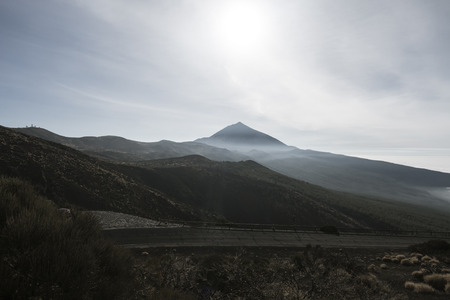 The Pico del Teide behind fog against the light in Tenerife, Spain seen from an observation point in La Tarta.