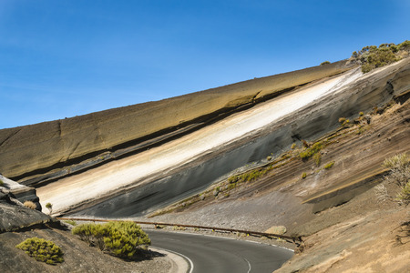 Colorful volcanic rock layers in a bend of the TF24 road in Tenerife, Spain. Stock Photo