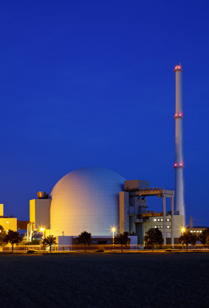 Reactor building of a large nuclear power plant with night blue sky.