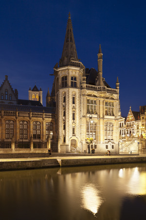 Backside of the old post office building in Ghent, Belgium with night blue sky and reflection.