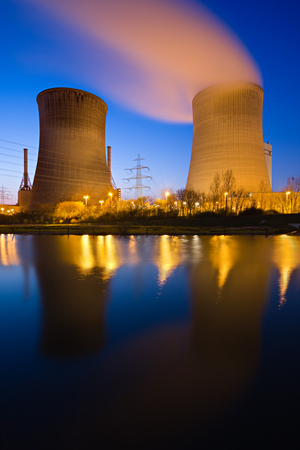 Twin pair of cooling towers with reflection at night. Stock Photo
