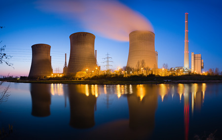 three generations: A coal-fired power station with reflection and beautiful night blue sky.