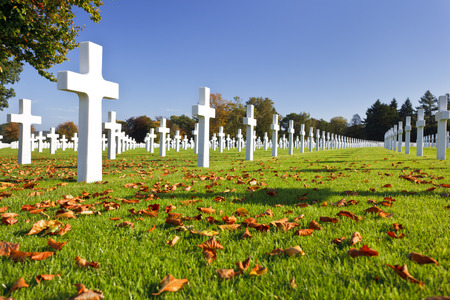 Blue sky and sunshine at the American military cemetery Henri-Chapelle near Aubel in Belgium, some foliage in the foreground.