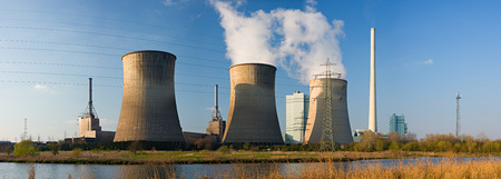 tall chimney: Panoramic shot of a coal-fired power station with three cooling towers in warm sunlight.