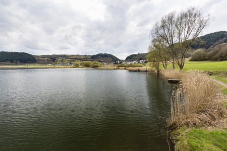 View alongside the shore of the Meerfelder Maar volcano lake in the Eifel, Germany on an overcast spring day. Stock Photo