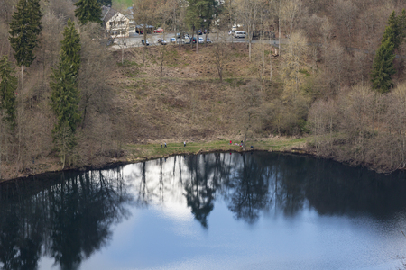 People at the Gemuendener Maar volcano lake in the Eifel, Germany near Daun in spring seen from the crater rim.