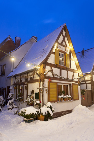 An alley with half-timbered houses and christmas lights at night during snowfall in Lachen, Neustadt an der Weinstrasse, Germany.