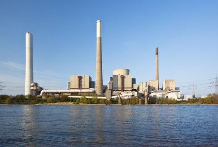 View over Rhine river to a giant coal power station with reflection.