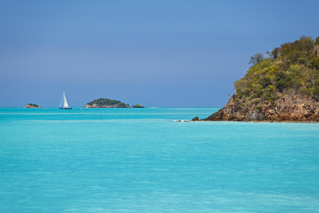 A small sailboat cruising between islands in turquoise sea.
