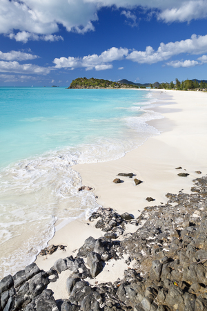 Beautiful Ffryes Beach in Antigua with rocks in the foreground.