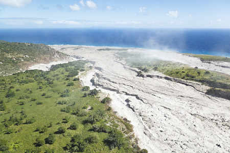 The dusty and steaming remains of recent pyroclastic flows of the Soufriere Hills Volcano in Montserrat. Aerial view from helicopter. Stock Photo