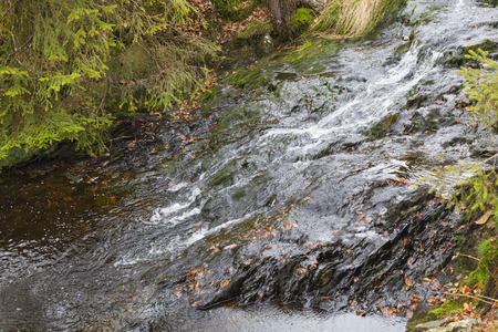 View of small waterfalls of the mountain creek Tro Maret running over slate rock in the Ardennes, Belgium with some brown old leaves. Stock Photo