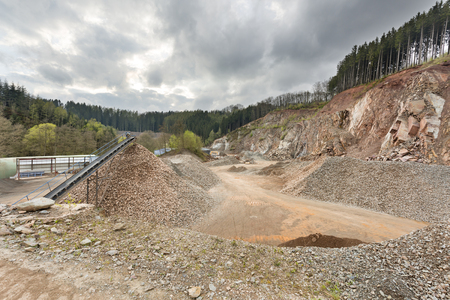 A large quarry in the Ardennes, Belgium with dark clouds, a rest of forest on the hill top.
