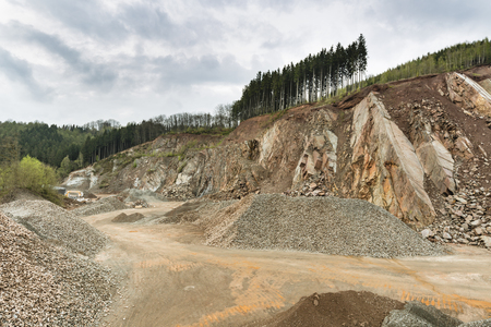 A large stone pit in the Ardennes, Belgium with dark clouds, a rest of forest on the hill top.
