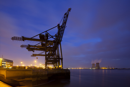 A container terminal with tall cranes with a nuclear power station in the background. Night shot taken in Antwerp, Belgium.