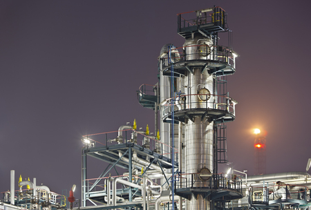 An oil refinery detail shot with a flare in the background. 에디토리얼